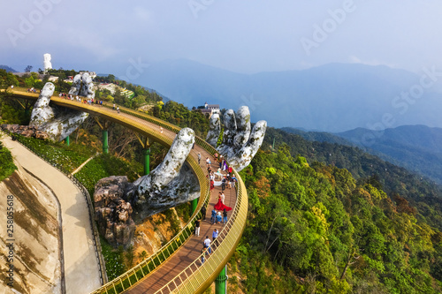 Fotografie, Obraz  Top aerial view of the famous Golden Bridge is lifted by two giant hands in the tourist resort on Ba Na Hill in Danang, Vietnam