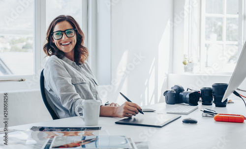 Professional photographer at her office desk