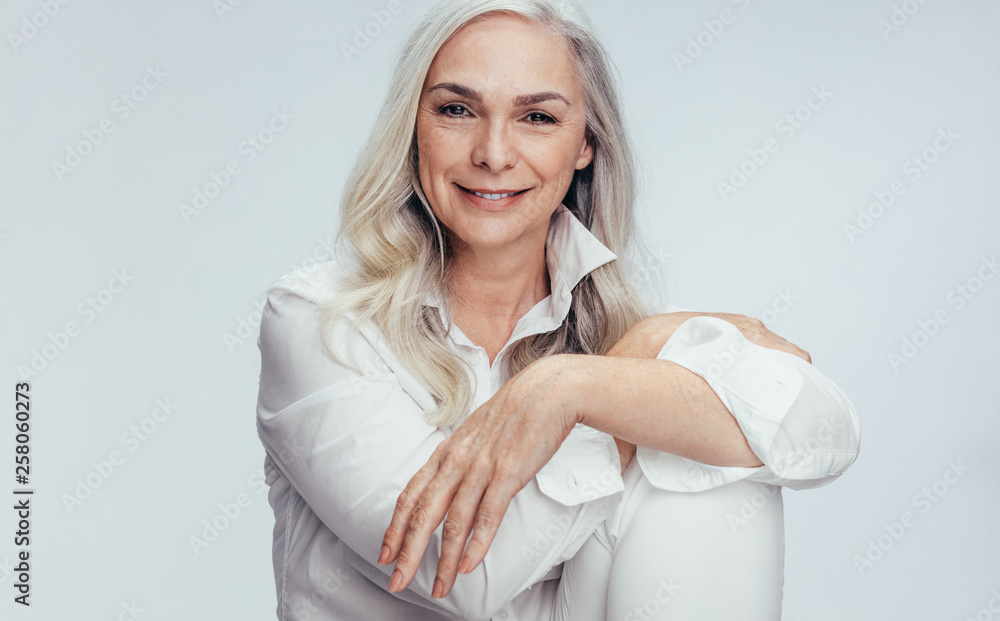 Fototapety, obrazy: Beautiful mature woman sitting over white background