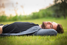 Young Teenage Man Sleeping In The Park, Lying Down In The Grass, Relaxing In Nature