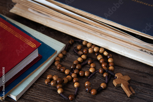 Valokuva Wooden rosary beads on old books. Wooden background