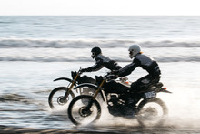 Two Friends Racing On Custom Retro Style Cafe Racer Black Motorcycles On The Beach At Sunset In Tabanan, Bali, Indonesia