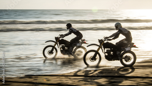 Fotomural Two friends racing on custom retro style cafe racer black motorcycles on the bea