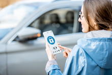 Woman Locking Car Using Mobile Application On A Smart Phone. Concept Of Remote Control And Car Protection Through The Internet