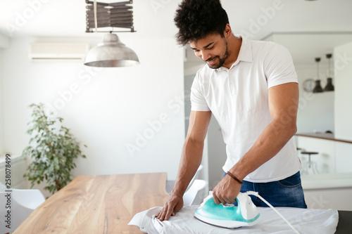 Valokuvatapetti Young Happy Man Ironing Clothes