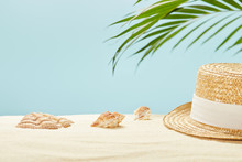 Selective Focus Of Straw Hat Near Seashells And Green Palm Leaf In Summertime Isolated On Blue