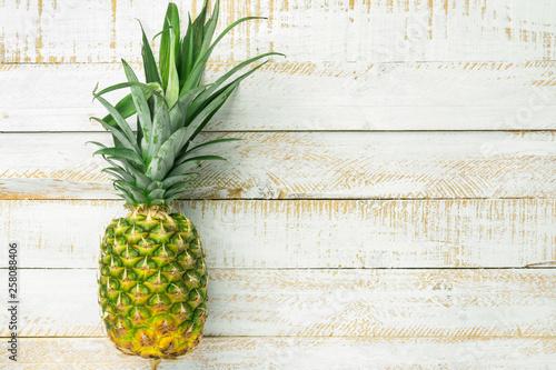 Valokuva  Ripe juicy whole pineapple on white wooden table