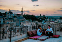 Happy Couple With A Drink On Rooftop Of An Cave House Historical Village Of Ayvali Goreme Cappadocia, Couple Watch Sunset Kapadokya
