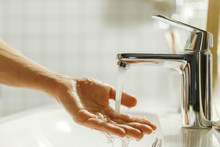 Man Washing And Cleaning Her Hand In Bathroom, Soft Focus. Closeup Of Fingers Under Flowing Tap Water. Hygiene, Bedtime Procedures