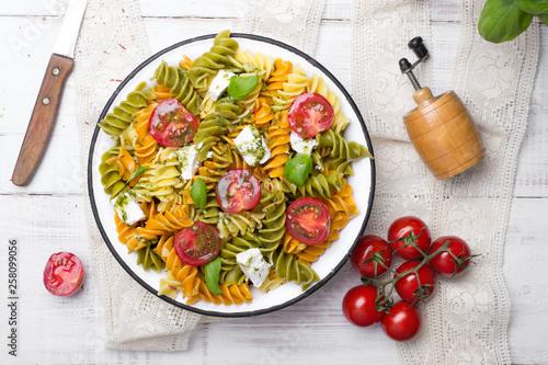 Fototapeta Italian food - Salad with colorful pasta, cherry tomatoes, feta cheese and fresh basil on white wooden background obraz