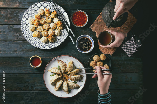 Photo  Family or friends dinner with Dim sum Gyozas asian fried dumplings set, variety of sauces served in ceramic plates with chopsticks, tea cups and teapot