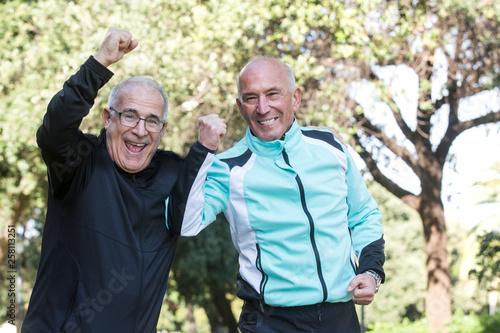 Photo Gruppo di amici anziani festeggia e si diverte al parco in tuta da ginnastica