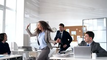 Young Energetic Businesswoman Walking To Colleagues Sitting At Their Desks In Office And Inviting Them To Dance Together: Team Joining Her And Dancing In Conga Line With Full Energy