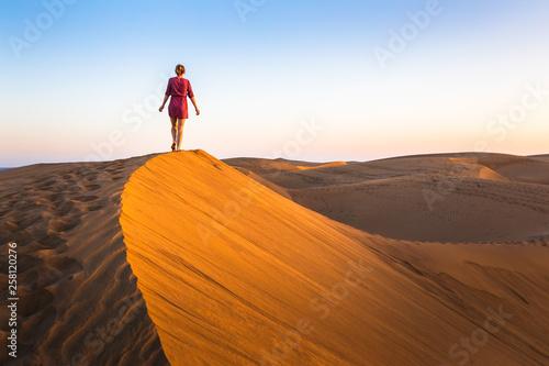 Girl walking on sand dunes in arid desert at sunset and wearing dress  scenic landscape of Sahara or Middle East