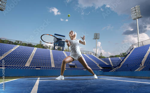 Fotografie, Obraz  Beautiful female tennis player serving outdoor on professional tennis court