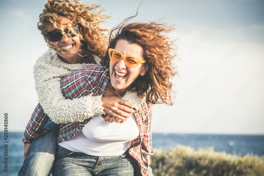 Fototapety, obrazy: Portrait of two pretty woman enjoy free time. Smiling middle age girls giving her laughing friend piggyback while enjoying the day together at the beach. Best friends smiling and playing together