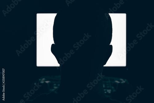 Fotografie, Obraz  Silhouette of man head in front of computer monitor light in dark room