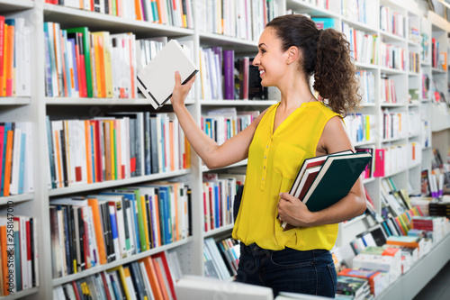 Photographie  Young glad woman holding books in hard cover