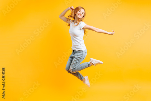 Portrait of a cheerful enthusiastic girl in a white T-shirt jumping for joy on a Wallpaper Mural