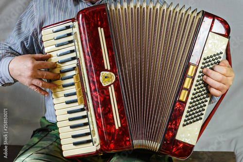 Fotografía  An old accordion is fun to play in the hands of an elderly musician