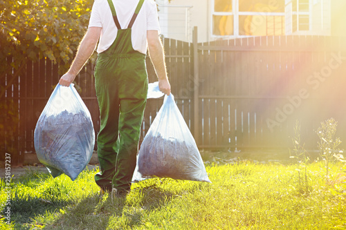 Fotomural Gardener carries bags of leaves after cleaning the yard