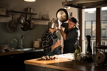 Friends Having A Duel With A Colander And A Pan In The Kitchen