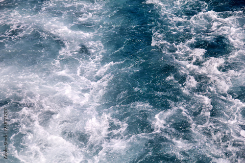Autocollant pour porte Turbulence made by foam of sea water from a high-speed yacht on surface of sea. Blue sea waves with lot of sea foam. Surface of sea with waves, splash, foam and bubbles, blue background and wallpaper.