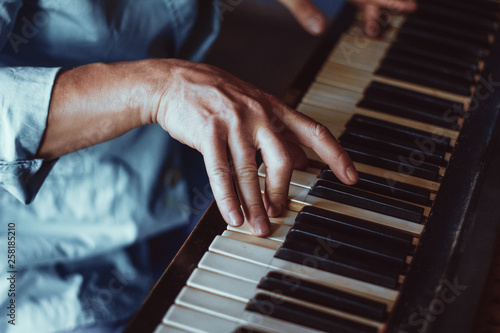 Male's hand playing a piano. Close-up. Music - 258185210