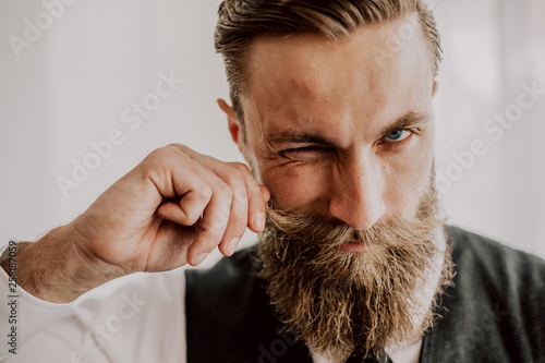 Obraz Handsome bearded hipster playing with his mustaches - fototapety do salonu