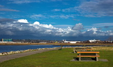 Picnic Area With Dining Tables An The River Bank Of Fraser River, Vancouver Airport On The Opposite Bank Of The River, Residential Areas Of Vancouver City On The Horizon Against A Cloudy Sky