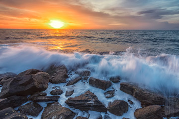 FototapetaStunning seascape with the colorful sunrise sky and beauty waves at the rocky coastline of the Black Sea