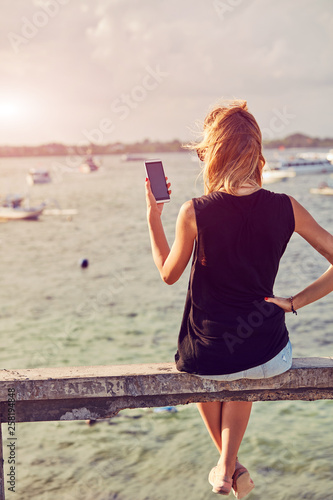 Fotografía  Attractive woman using cellphone while sitting near sea/ocean.