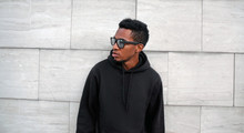 Portrait African Man In Black Hoodie, Sunglasses Looking Away On City Street Over Gray Brick Wall Background