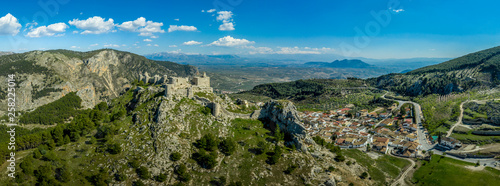 Foto  Moclin medieval walled town and ruined castle with blue sky aerial panorama