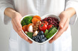 Doctor holding bowl with products for heart-healthy diet, closeup