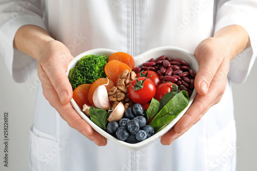 Photo  Doctor holding bowl with products for heart-healthy diet, closeup