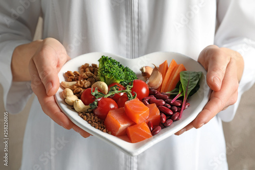 Fotografia Doctor holding plate with products for heart-healthy diet, closeup