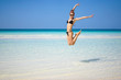 Portrait of beautiful young woman jumping in air at the beach.