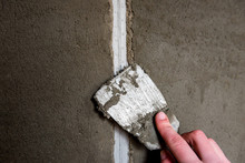 Plasterer Sealing Joint Of Building Wall With Putty Knife.