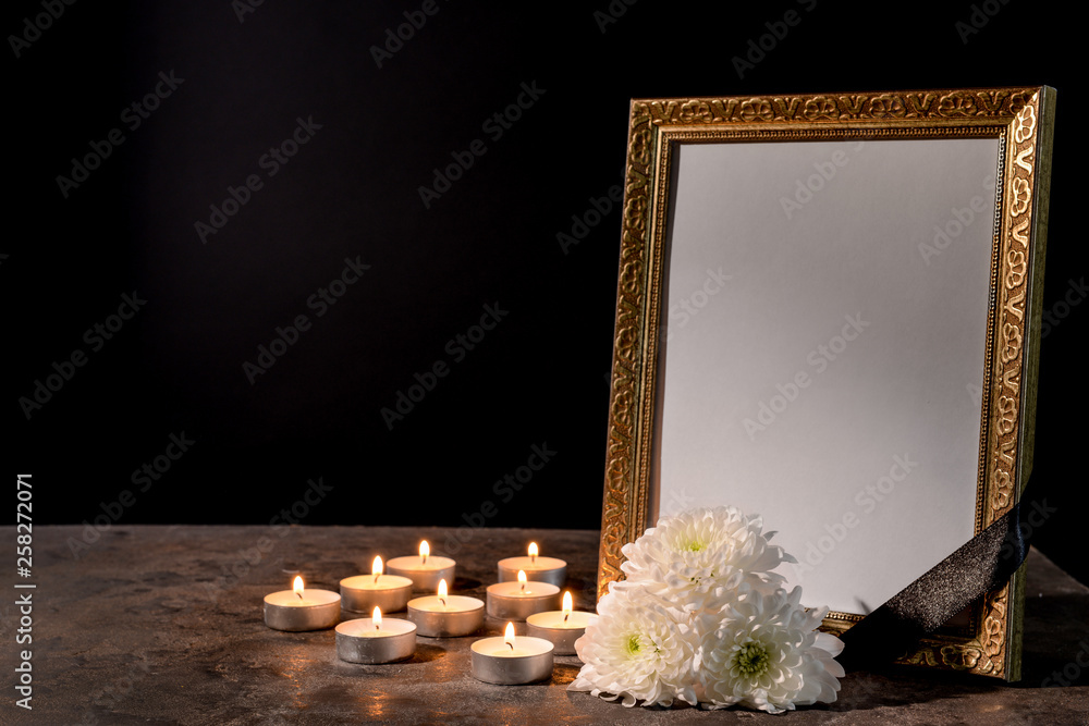 Fototapety, obrazy: Blank funeral frame, candles and flowers on table against black background