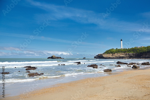Foto auf Gartenposter Blau Jeans Sandy ocean beach and white lighthouse, located in Biarritz, France