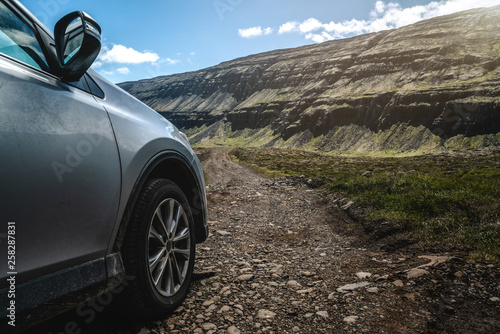 Garden Poster Brown 4WD SUV vehicle car running on gravel road with nature mountain landscape in Iceland. Adventure and extreme sport.