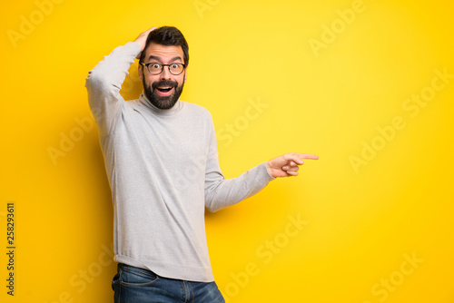 Fotografía Man with beard and turtleneck pointing finger to the side and presenting a produ