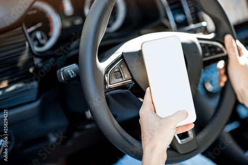 Foto auf Leinwand Akt Woman holding a smart phone with empty screen to copy paste while driving a car on the steering wheel