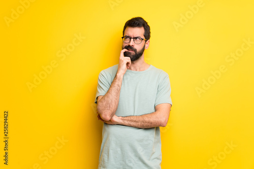 Obraz na plátně Man with beard and green shirt having doubts while looking up