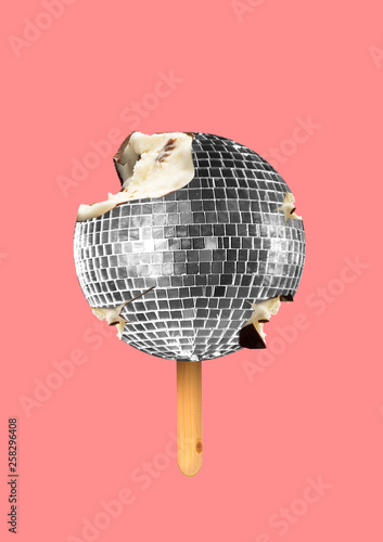 A musicial icecream. A silver disco ball as a sweets filled with cream and covered with chocolate on wooden stick on coral background. An alternative food. Modern design. Contemporary art collage.