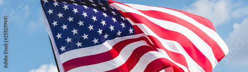 Fototapeta panoramic shot of american flag with stars and stripes against blue sky obraz