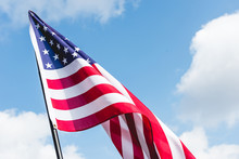 Low Angle View Of Stars And Stripes On American Flag Against Blue Sky With Clouds