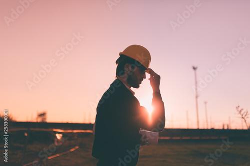 Fotografie, Obraz  Sagoma laterale di un giovane ragazzo ingegnere che si mette il caschetto giallo con la mano prima di entrare in cantiere al tramonto