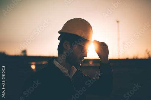 Sagoma laterale di un giovane ragazzo ingegnere che si mette il caschetto giallo con la mano prima di entrare in cantiere al tramonto Tapéta, Fotótapéta